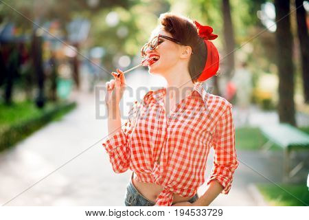 Sexy pin up girl with lollipop walks in a park