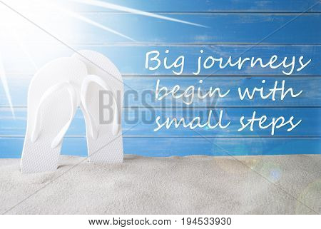 English Quote Big Journey Begin With Small Steps. Sunny Summer Greeting Card With Sand And Flip Flops. Blue Vintage And Shabby Chic Wooden Background.