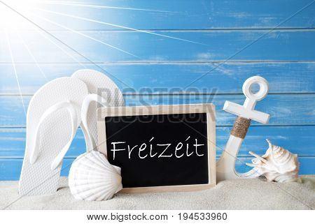 Chalkboard With German Text Freizeit Means Leisure Time. Blue Wooden Background. Sunny Summer Card With Holiday Greetings. Beach Vacation Symbolized By Sand, Flip Flops, Anchor And Shell.