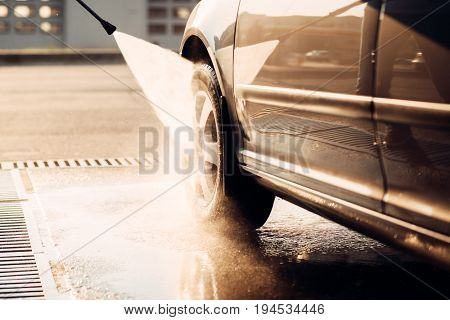 Male worker wash the car with high pressure washer