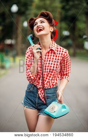 Smiling pinup girl with retro rotary phone