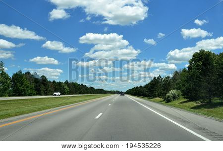 Highway with cars in distance sunny skies with a few puffy clouds