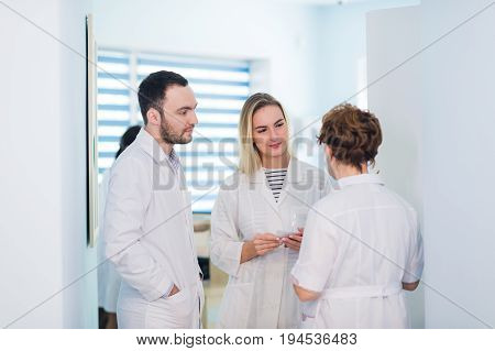 Mature doctor discussing with nurses in a hallway hospital. Doctor discussing patient case status with his medical staff after operation