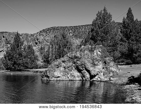 A giant partially submerged boulder extends from the shore into the waters of Prineville Reservoir in Central Oregon on a clear summer morning.