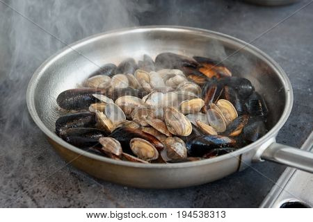 Clams and mussels on hot pan at commercial kitchen