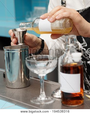 Bartender is pouring homemade infusion into a mixing glass, making cocktail