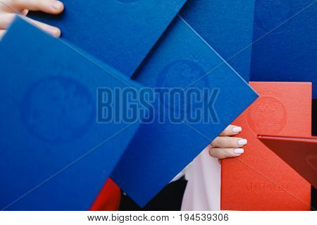 Red and blue diplomas of Higher Education University in hands Russia. Inscriptions in Russian: Russia. Diploma