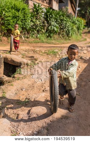 Hsipaw, Myanmar - October 6, 2016: Little burmese boy playing with the bike tyre in the village near Hsipaw, Myanmar (Burma)
