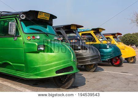 Ayutthaya, Thailand - March 3, 2017: Vintage Tuk Tuk taxi in Ayutthaya historical park. A traditional three wheel taxi car in Ayutthaya, Thailand