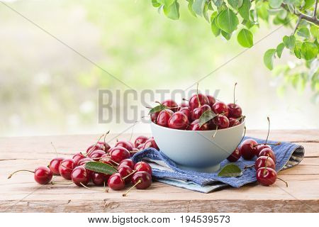 Ripe cherry in a plate on a wooden board on a background of green leaves