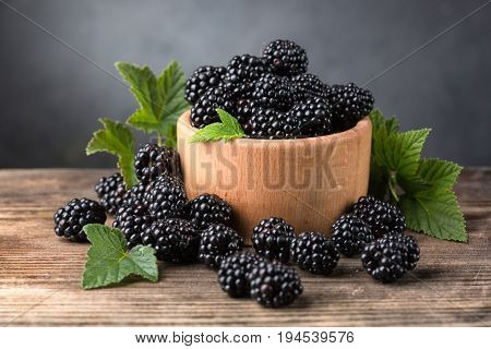 Ripe blackberries with leaves in a bowl on a wooden background