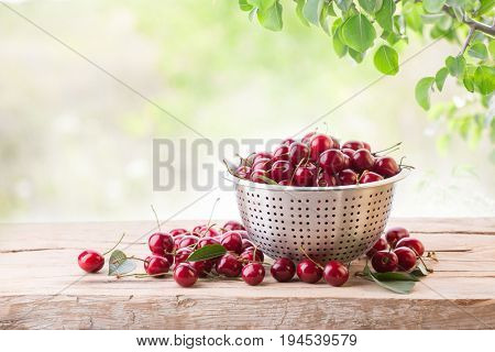 Ripe cherry in a colander on a wooden board on a background of green leaves