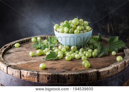 Ripe gooseberry in a bowl on a wooden background
