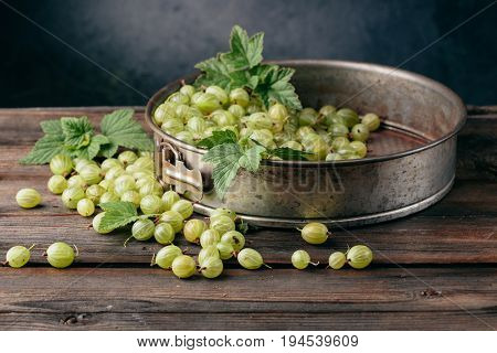 Ripe gooseberry in a plate on a wooden background