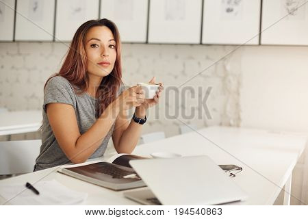 Young writer relaxing drinking coffee skimming through magazine in a bright studio space.