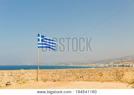 Rethymnon Greece Crete Island old Citadel Fort Fortezza fortress wall develops Greek flag on the background of the Mediterranean Sea