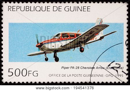 Moscow Russia - July 07 2017: A stamp printed in Guinea shows light aircraft Piper PA-28R-180 Cherokee Arrow in flight series