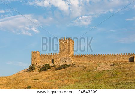 Krym Sudak ruins of an old fortress on a green hill with a piece of gear stone walls. Genoese fortress