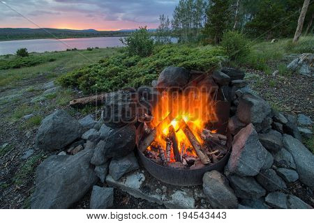 A campfire burns hot during the evening at a lakeshore campsite in the mountains.