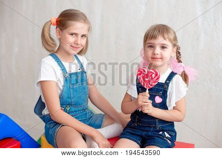Two adorable little sisters laughing and hugging each other taking lollipop. Great sister's love.