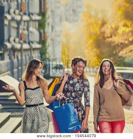 Three happy shoppers walking with packages of new clothes. image with toning