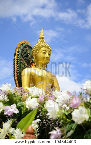 Buddha statue with floral arrangement on bright sky background.