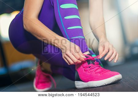 Woman tying shoelaces. Pink sneakers. Purple tights