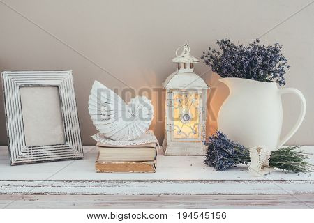 Shabby chic interior decor for farmhouse. Lavender in pitcher, books and lantern on a vintage shelf over pastel wall. Provence home decoration.