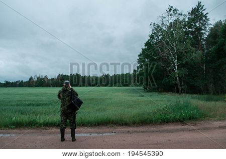 photographer-naturalist, a man in camouflage clothes with a backpack, a photographer in the background on a cloudy day