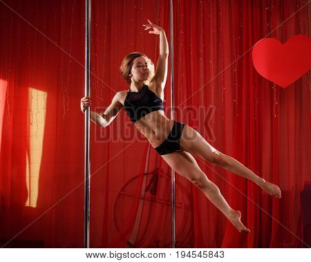 Sexy pole dancer performs on a pylon. She jumped. Flexibility plasticity and strength.