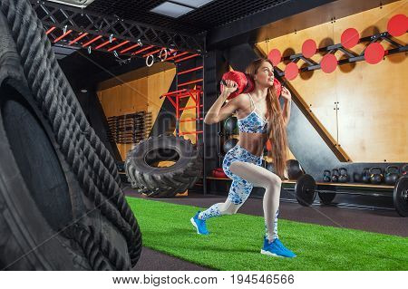 Young beautiful sporty woman doing lunges with a sandbag. Woman doing exercises in the gym