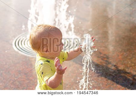 Funny Baby Boy Trying To Cauch Water Stream In Fountain. Cute Toddler Playing In The City Fountain