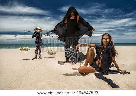June 23, 2017 PhanThiet, VietNam. Beautiful couple wearing in black costumes relaxing At Beach in VietNam and Unidentified women carrying fruits for sale looking at them