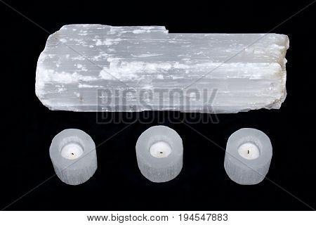 Natural decorative selenite log and selenite cylinder tea light holders on black fabric background