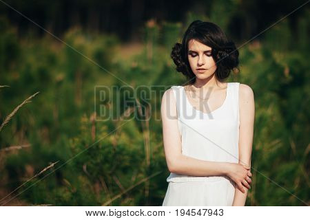 Fashion model. Girl with cute braided hairstyle posing in nature on green blured background