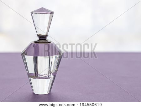 Empty vintage crystal glass perfume bottle with stopper on lilac background