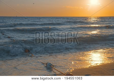Sunset on a sandy beach. Sea waves and a rope with buoys on the shore