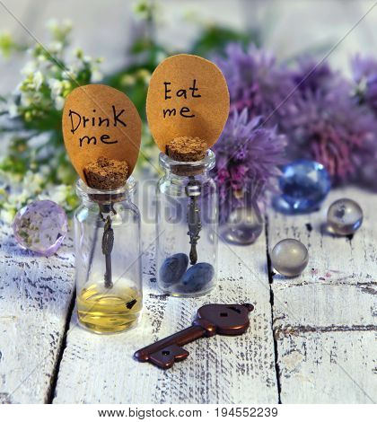 Close up of cute bottles with labels eat me and drink me, key, crystal balls and flowers. Alice in Wonderland background, fairy tale abstract concept with summer flowers