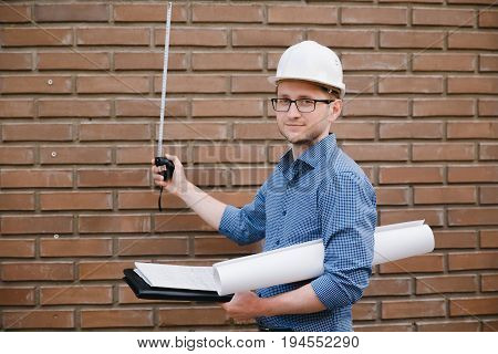 Male construction builder worker - foreman is an engineer in a protective helmet, glasses on the background Brick wall ruler measures. Concept calculation of construction time and cost. copyspace