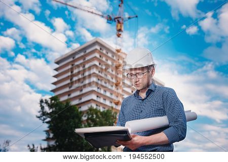 Male construction builder worker - foreman is an engineer in a protective helmet, glasses on the background of building a house with a crane. Concept writes down, calculates the estimate.