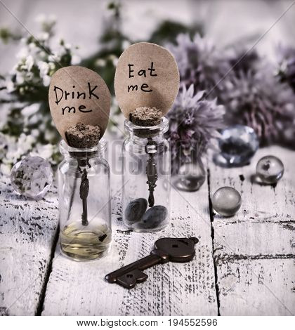 Toned close up of cute bottles with tags eat me and drink me, key, crystal balls and flowers. Alice in Wonderland background, fairy tale abstract concept with summer flowers