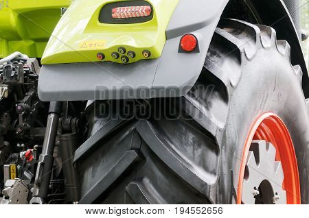 Wheeled tractor fragment close up horizontal outdoors background