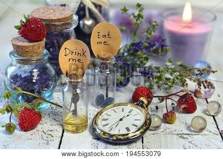 Glass bottles with tags eat me, drink me, vintage clocks, candle and summer berry on table. Alice in Wonderland background, fairy tale abstract concept with summer flowers