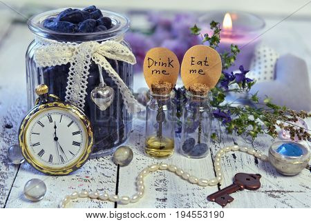 Vintage objects, tiny bottles with labels eat me and drink me, old clocks, key and honey berry in jar. Alice in Wonderland background, fairy tale abstract concept with summer flowers