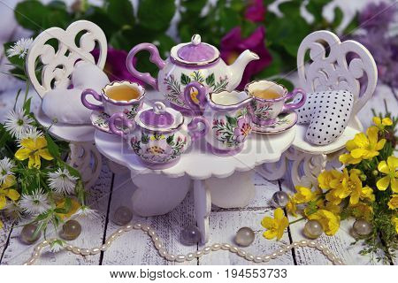 Mad tea party concept with small table, chairs, cups and teapot and with wild flowers. Alice in Wonderland background, fairy tale abstract concept. Still life of mad tea party
