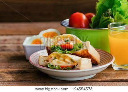 Pocket sandwich for breakfast or lunch.Homemade sandwich with hard boiled eggs and mayonnaise decorated by lettuce and tomato. Baked sandwich on lovely plate serve with orange juice on wood table. Delicious grilled sandwich ready to served.