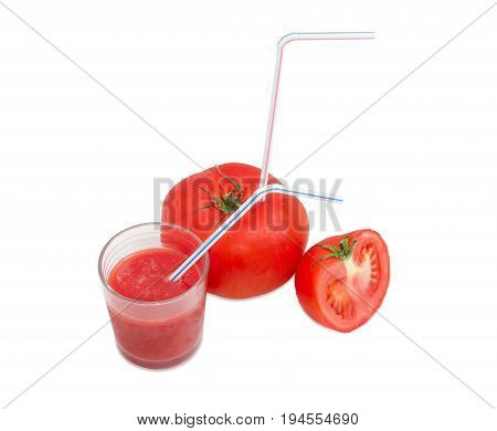Big fresh whole tomato with bendable drinking straw inserted into it half of the tomato and glass with tomato juice with drinking straw on a light background