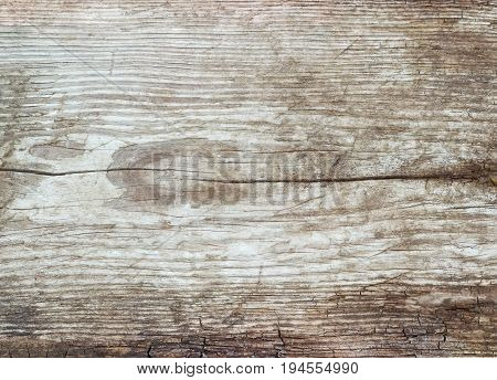 Background of a surface of the old dilapidated wooden plank covered by cracks and darkened with time