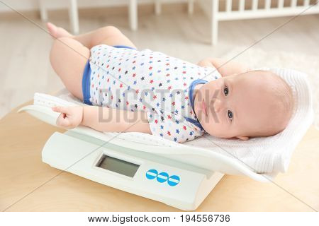 Baby lying on scales in room