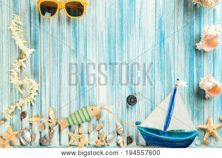Summer vacation concept. Beautiful composition with boat and shells on blue rubbed wooden background